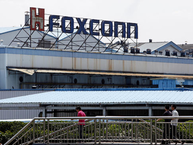 Workers walk outside Hon Hai Group's Foxconn plant in Shenzhen, Guangdong province, China, on Wednesday, May 26, 2010. Gou said nine of the 11 company workers who either committed suicide or attempted to had worked at the company less than a year, and six had been employed for less than a half-year. Photographer: Qilai Shen/Bloomberg